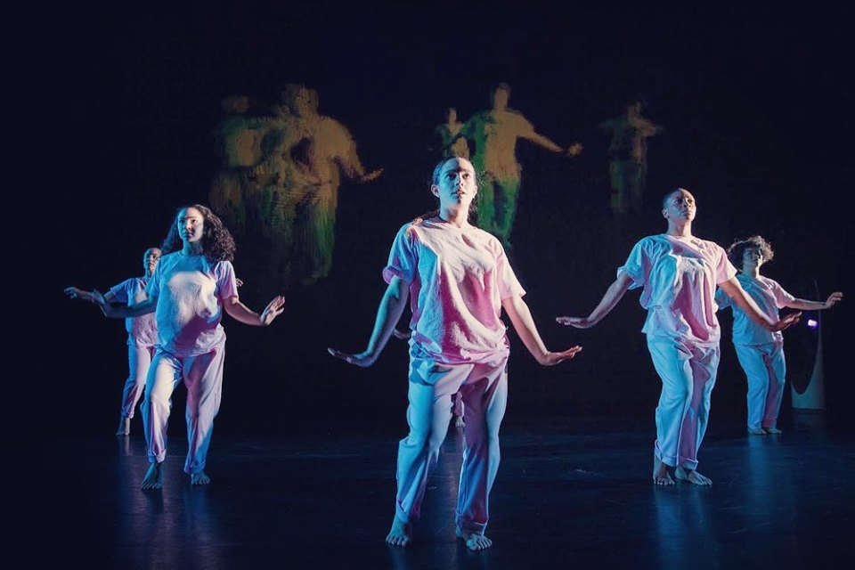 3 dancers in plain clothing in front of a projection of themselves
